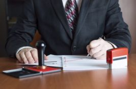 Notary Public in his office signing a contract